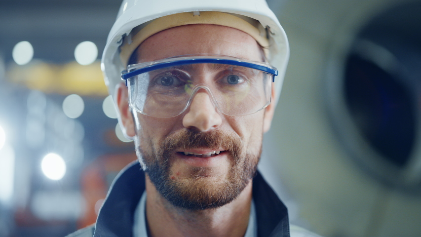 Portrait of Smiling Professional Heavy Industry Engineer / Worker Wearing Safety Uniform, Goggles and Hard Hat. In the Background Unfocused Large Industrial Factory | Shutterstock HD Video #1035704024