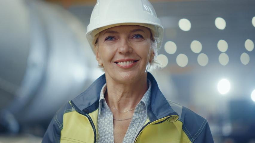 Portrait of Professional Heavy Industry Female Engineer Wearing Safety Uniform and Hard Hat, Smiling Charmingly. In the Background Unfocused Large Industrial Factory where Welding Sparks Flying | Shutterstock HD Video #1035704099
