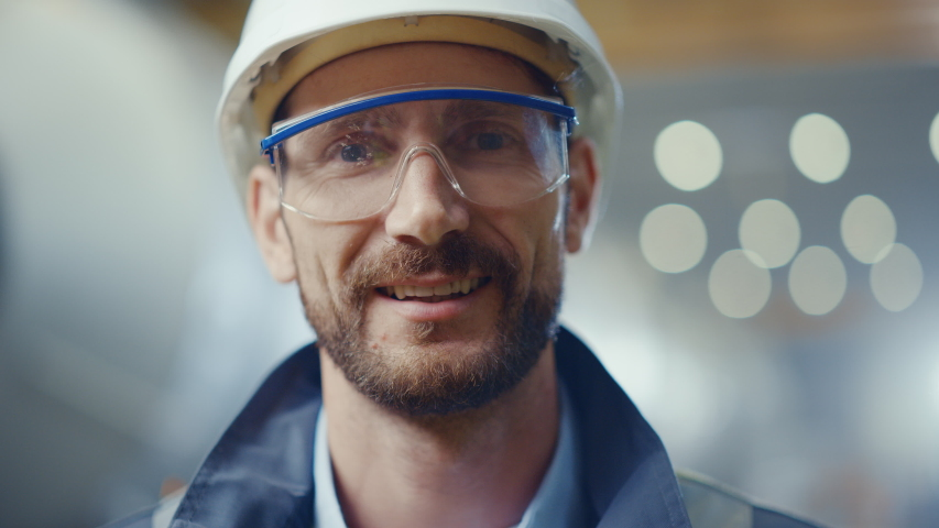 Portrait of Professional Heavy Industry Engineer / Worker Wearing Safety Uniform, Goggles and Hard Hat Smiling. In the Background Unfocused Large Industrial Factory where Welding Sparks Flying Royalty-Free Stock Footage #1035704111