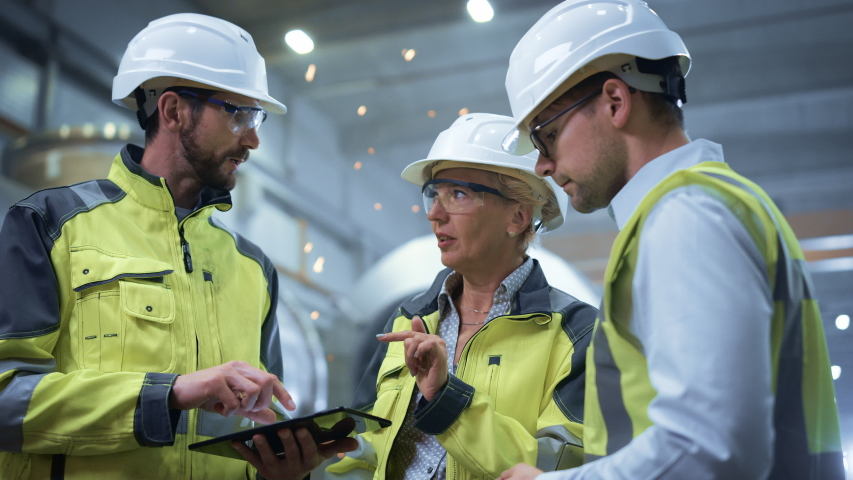 Three Heavy Industry Engineers Stand in Pipe Manufacturing Factory, Use Digital Tablet Computer, Have Discussion. Large Pipe Assembled. Design and Construction of Oil, Gas and Fuels Transport Pipeline Royalty-Free Stock Footage #1035704162