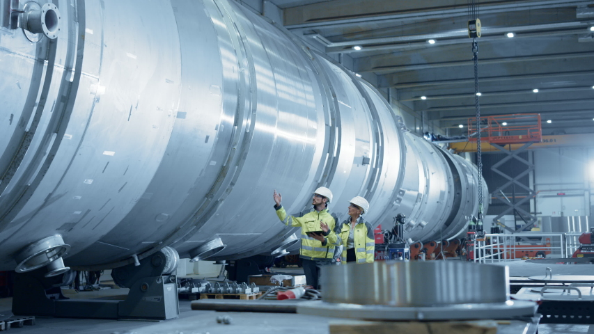 Two Heavy Industry Engineers Walking Through Pipe Manufacturing Facility, Use Digital Tablet, Have Discussion. Modern Industrial Design and Construction of Oil, Gas and Fuels Transport Pipeline