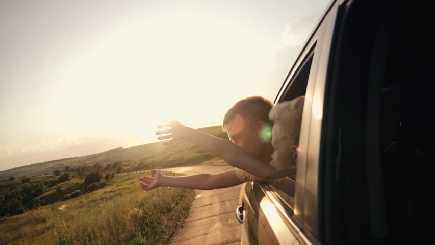 Happy family traveling by car. Two boys in the car window waving their hands in the sun at sunset. #1035706385
