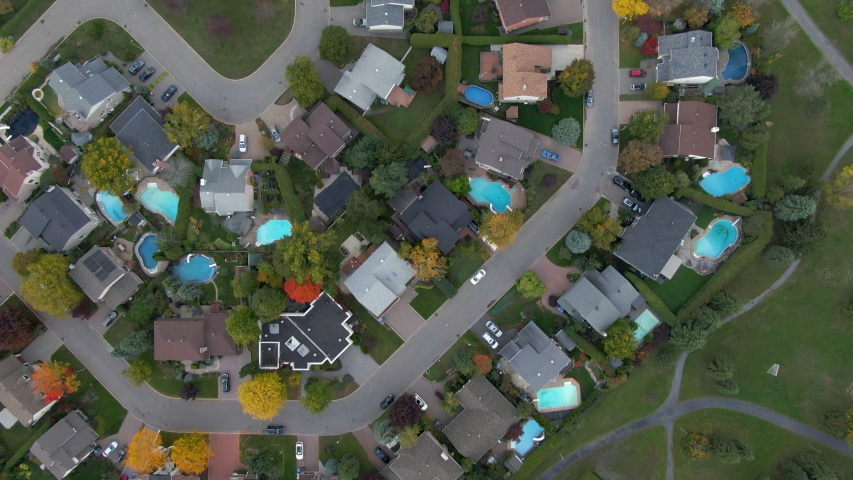 Fall in Montreal, Quebec, Canada, top-down aerial view of residential neighbourhood showing family homes and colourful maple trees in Autumn season.