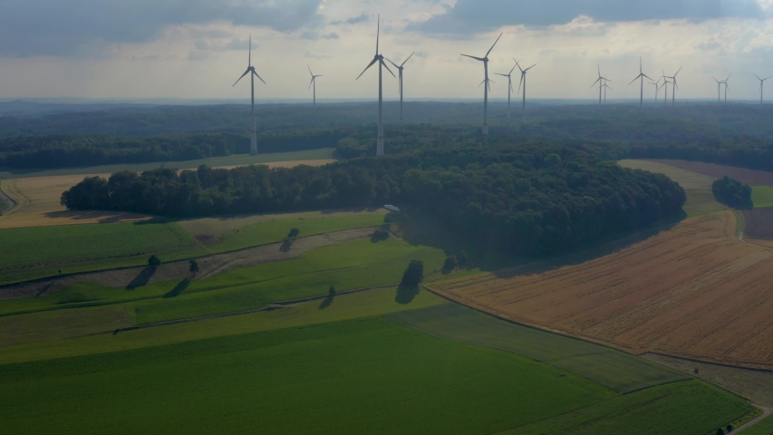 Aerial view of wind turbines close to Berlichingen in Germany. Wide view with zoom in from the side of the turbines. | Shutterstock HD Video #1035716363