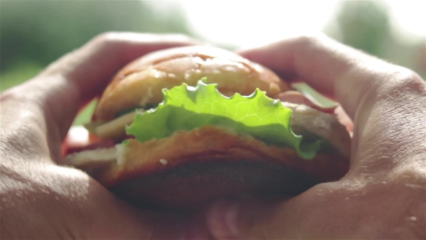 Man holding in hands tasty burger and eat first person view | Shutterstock HD Video #1035740753