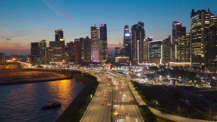 Hyperlapse aerial view flying backward of Road highway along to the night cityscape skyline at Singapore.
