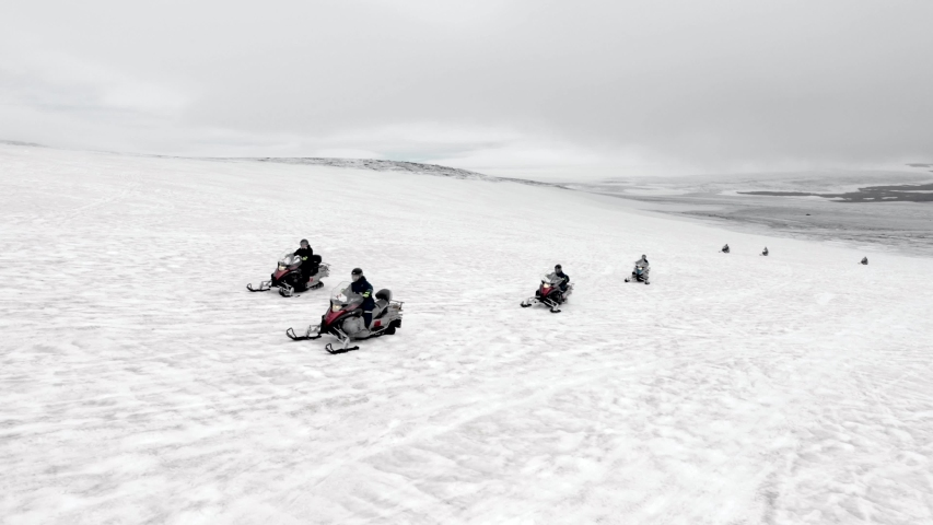 Aerial view of snowmobile tour driving in snowy hills.Arctic expedition atmosphere, north pole,winter landscape of Vatnajokull Glacier Iceland. Extreme sport,adventure and travel destination concept. | Shutterstock HD Video #1035761201