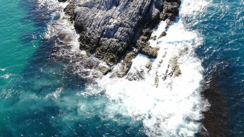 Waves hitting the cliffs on the rocky coast of the sea. Cliffs of blue turquoise sea. camera going forward. Aerial view drone shoot. 4k cinematic