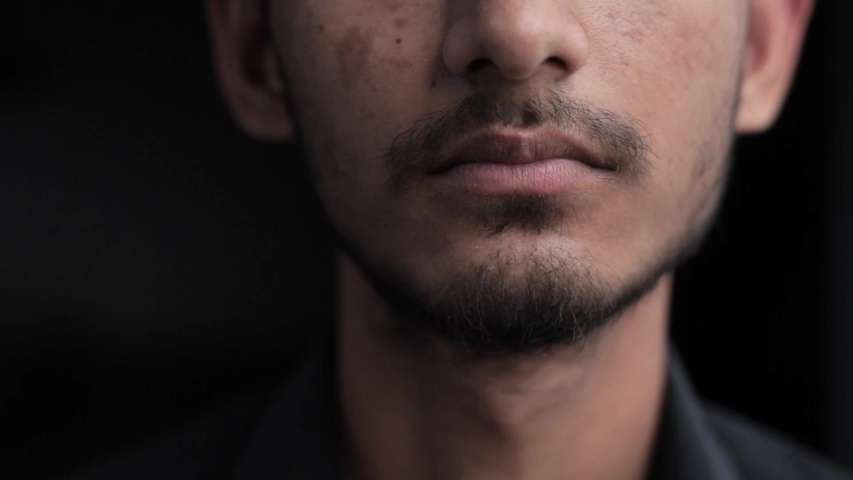 Close up shot of beard man isolated on black itching his beard with his hand with lots of space for ideal usage for advertisements. | Shutterstock HD Video #1035765050