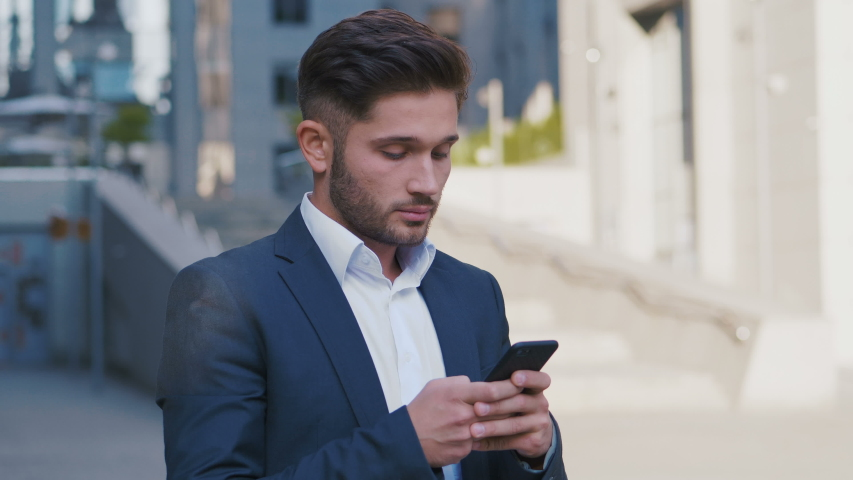 Young Handsome Businessman Standing near Big Office Building. Typing a Message on his Smartphone.Bearded Man Wearing Classical Suit. Business Lifestyle. | Shutterstock HD Video #1035767933