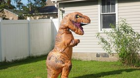 A man dressed in a funny blow-up dinosaur costume dances.