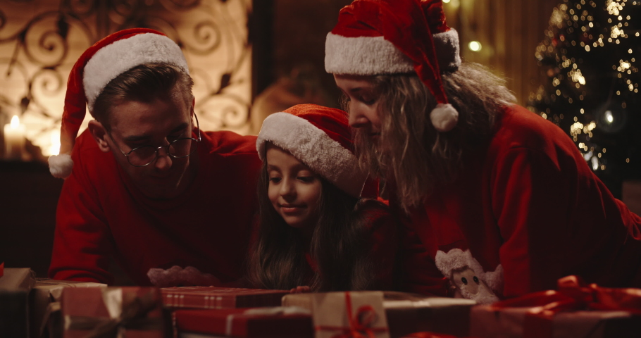 Caucasian family of three sitting in decorated room near christmas tree, little girl opening her christmas gift with something special - christmas spirit, togetherness concept 4k footage | Shutterstock HD Video #1035778853
