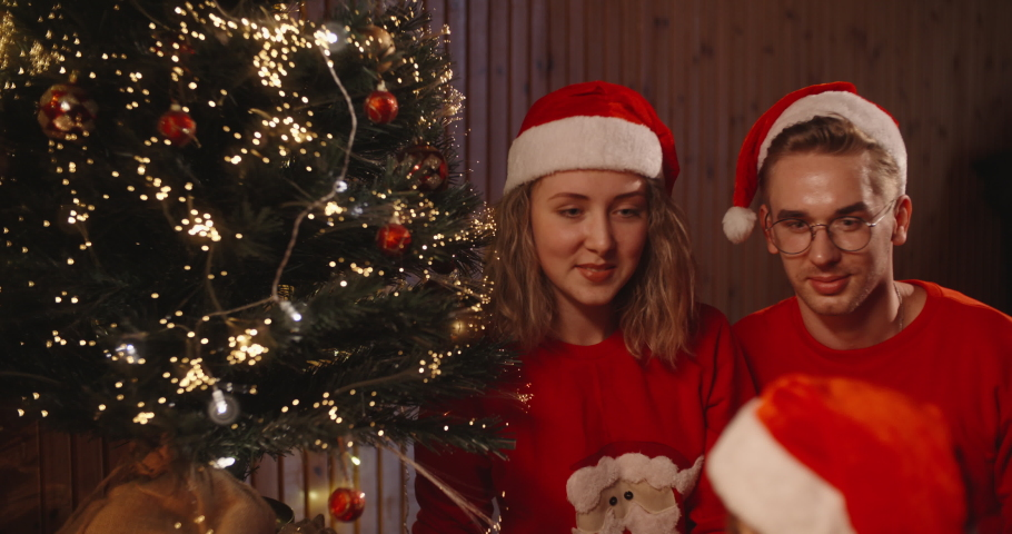Parents watching their little girl leaving cookies and milk near fireplace on christmas eve - holidays and celebrations, christmas spirit concept 4k footage