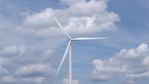 Wind turbine spins around for generating energy with clouds