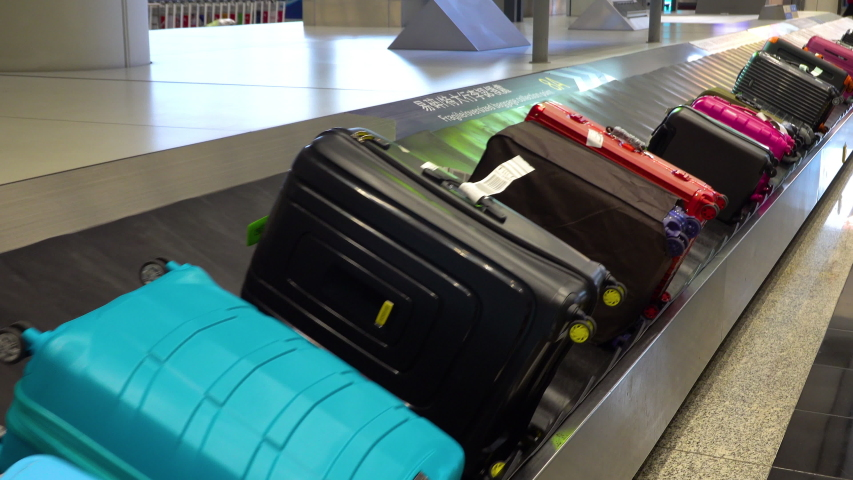 Various suitcases moving on the luggage conveyor belt at arrival area in the passenger terminal at Hong Kong International airport | Shutterstock HD Video #1035798917