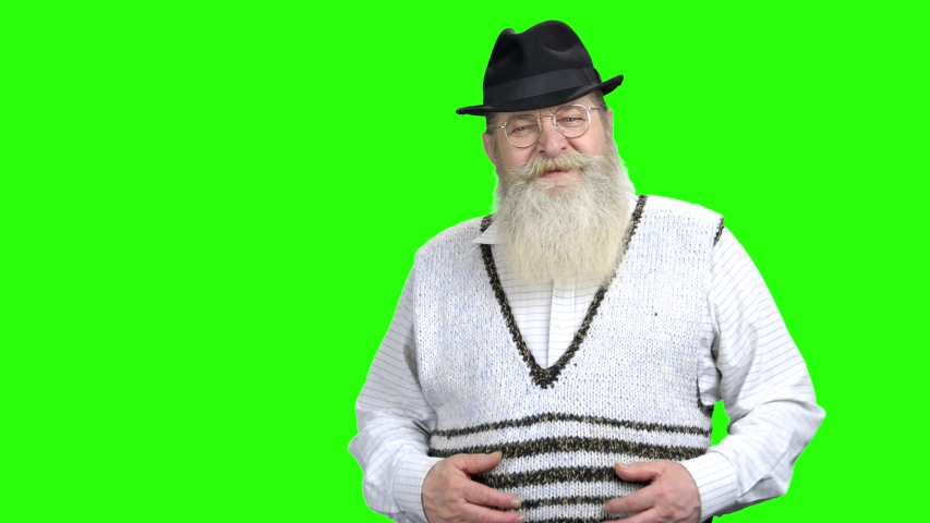 Happy senior man in hat giving thumb up. Portrait of good-looking old man with big beard and smile on green Chroma Key background.