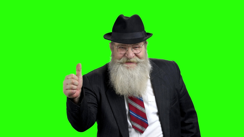 Handsome bearded businessman showing thumb up. Old man in suit and hat giving thumb up on green screen. Successful achievement concept.