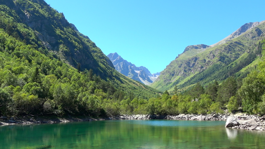 Lake scenes in mountains, national park of Dombay, Caucasus, Russia. Summer landscape, sunshine weather, blue sky and sunny day   Shutterstock HD Video #1035803105