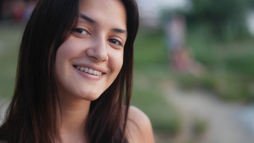 Portrait of young cute fit girl on the beach in scorching summer evening at sunset. Closeup of a pretty woman in Slow motion #1035808517