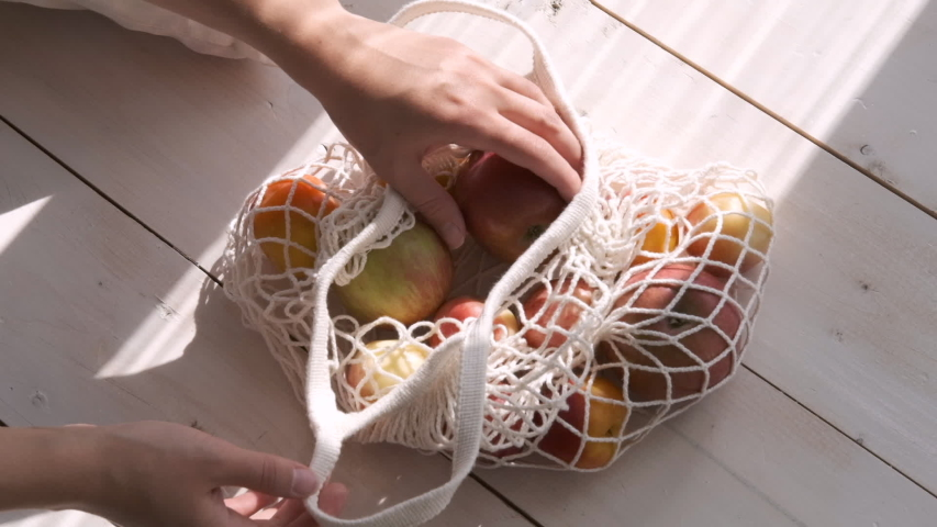 Zero waste home and eco bag. Eco Shopping. Reusable grocery bags with fruits and vegetables on the kitchen on wooden table. Slow motion