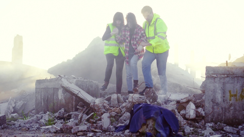 Portrait rescuers in uniform help the victim of the earthquake ,pulling her out from under the ruins of the house