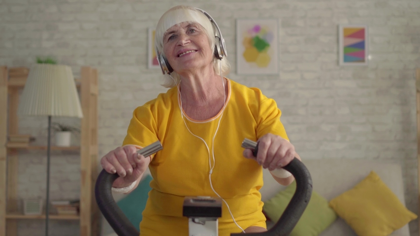 Portrait active old woman in headphones engaged in cardio training on a exercise bike