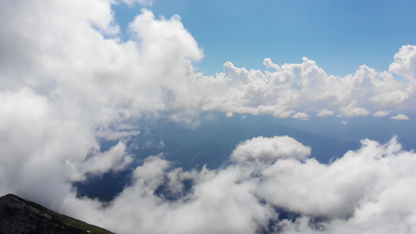 Flying through amazingly beautiful cloudscape. Picturesque timelapse of white fluffy clouds moving softly on the clear blue sky in pure sunshine. Direct view from the cockpit. Royalty-Free Stock Footage #1035816071