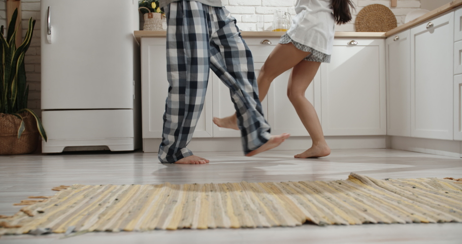 Low angle shot of unrecognizable couple crazily dancing in kitchen during their pajamas party - recreational pursuit 4k
