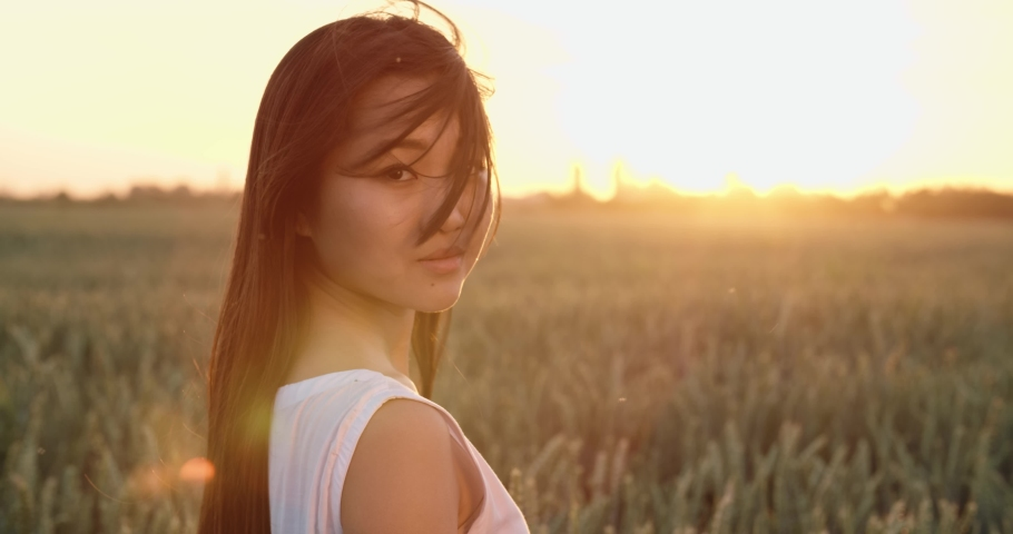 Close up portrait shot of pretty asian girl walking in wheat field during sunset, looking at camera and smiling 4k footage   Shutterstock HD Video #1035824741