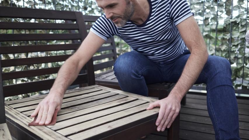 Panning shot of man sitting on apartment terrace sanding wooden garden chair   Shutterstock HD Video #1035832679