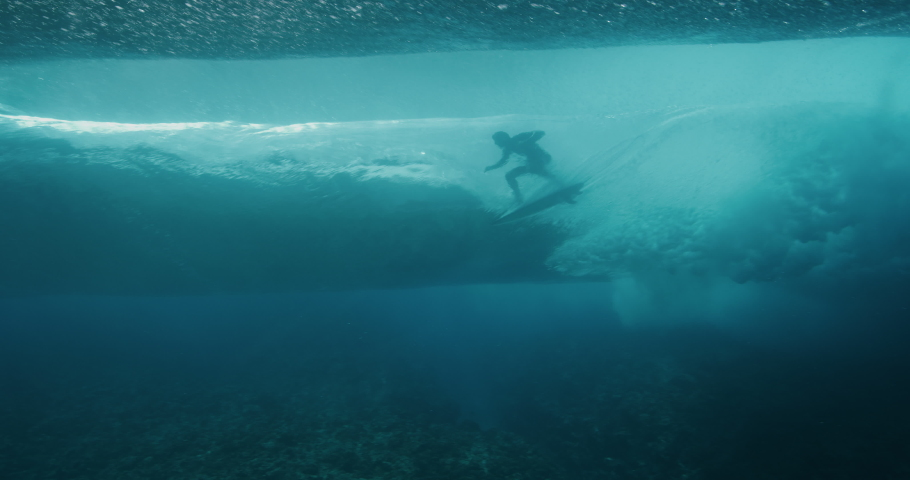 Underwater shot of a surfer's silhouette riding the barrel of a perfect blue ocean wave | Shutterstock HD Video #1035869150