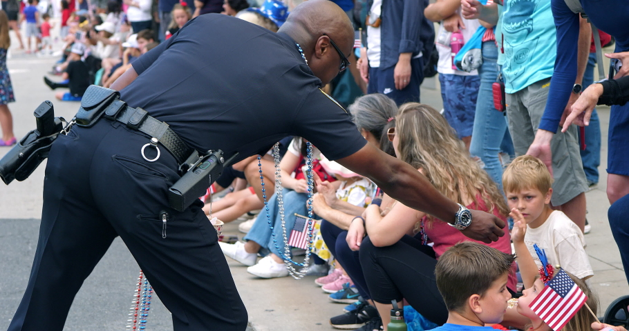 LOS ANGELES, CALIFORNIA, USA - JULY 4, 2019: Afro-American Los Angeles Police Department officer gives children candies at Independence Day parade in Los Angeles, California, 4K