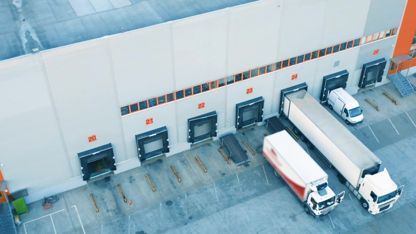 Aerial view of a semi-trailers trucks standing at the warehouse ramps for load/unload goods in the logistics park  | Shutterstock HD Video #1035882002