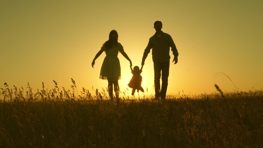 little daughter jumping holding hands of dad and mom in park on background of sun. Family concept. child plays with dad and mom on field in sunset light. Walking with small kid in nature.