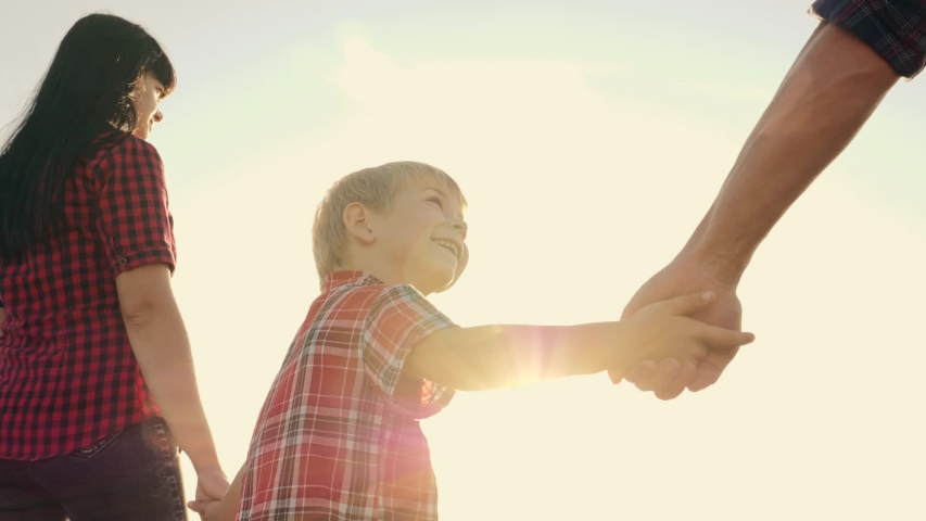 Happy family walks in the park in the sun at sunset. Mom, dad and baby happy walk at sunset. Joint family walks healthy lifestyle. The concept of a happy family and family values | Shutterstock HD Video #1035893210