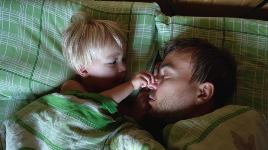 Cute toddler son and father sleeping together on bed in bedroom at home, little boy wake up their dad.