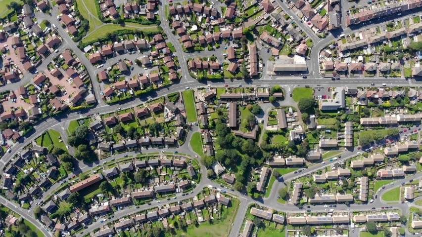 Aerial footage of the British town of Middleton in Leeds West Yorkshire showing typical suburban housing estates with rows of houses, taken on a bright sunny day using a drone.