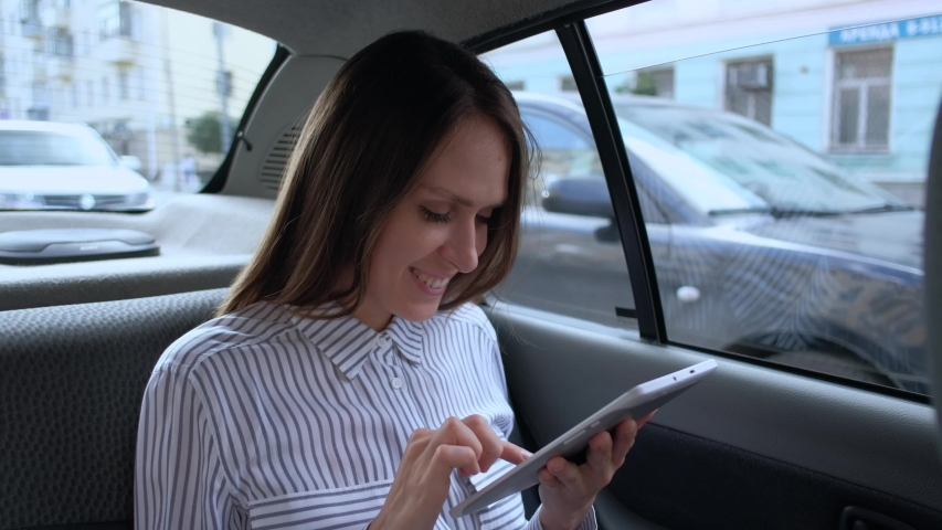Young beautiful woman using a digital tablet sitting in backseat car taxi. Happy young woman using a tablet in a car.