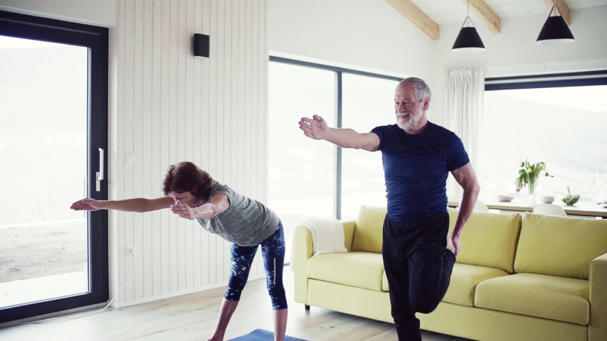 A senior couple indoors at home, doing exercise indoors. Slow motion. | Shutterstock HD Video #1035914345