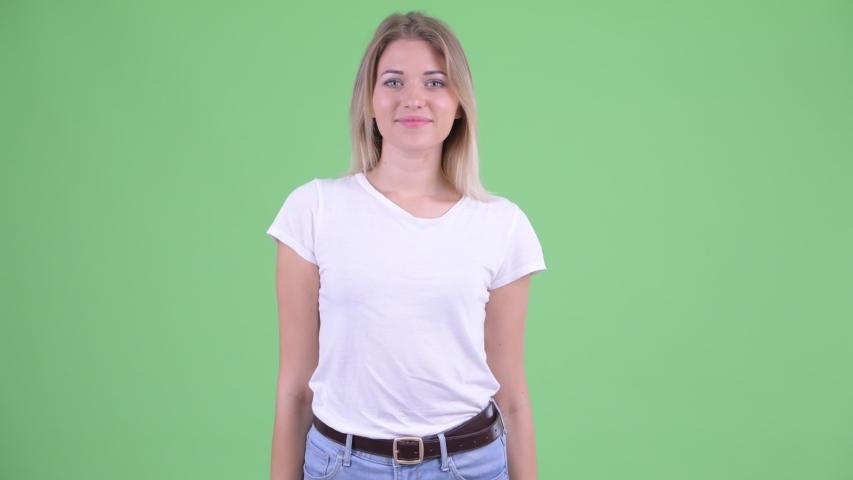 Happy young beautiful blonde woman waving hand | Shutterstock HD Video #1035919796