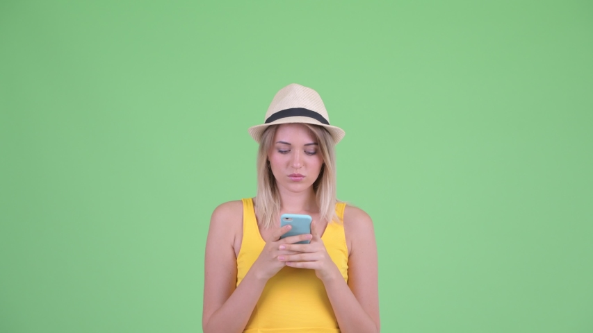 Happy young blonde tourist woman using phone and looking surprised   Shutterstock HD Video #1035919835