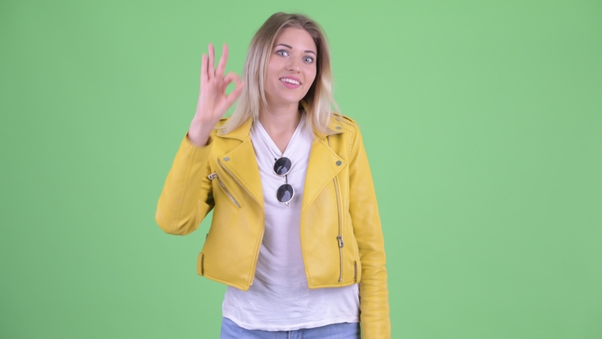 Happy young rebellious blonde woman with ok sign | Shutterstock HD Video #1035920057