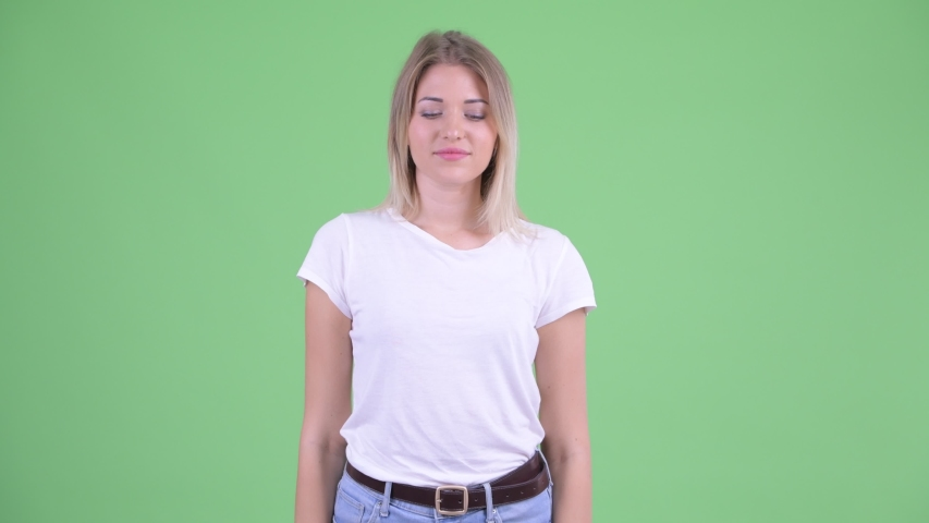 Confused young blonde woman choosing between thumbs up and thumbs down | Shutterstock HD Video #1035920135