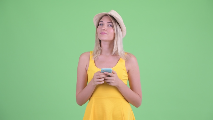 Happy young blonde tourist woman thinking while using phone   Shutterstock HD Video #1035920360