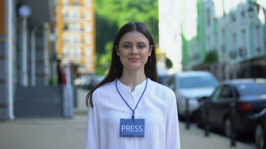 Female journalist with microphone and press pass looking at camera on street | Shutterstock HD Video #1035924398
