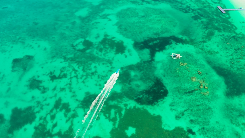 Lagoon with turquoise water and speed boat, copy space for text, top view. Tropical lagoon with clear and azure water. Summer and travel vacation concept. Boracay Island, Philippines