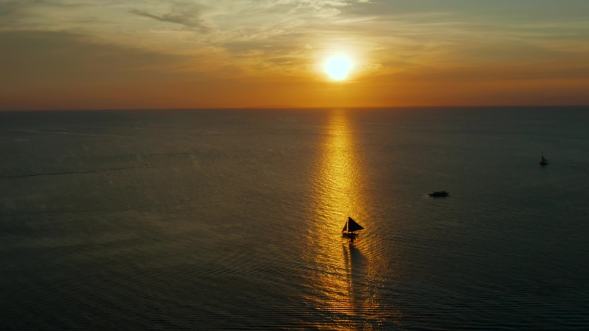 Colorful sunset above the sea surface with sailing yachts, aerial view Boracay, Philippines. Reflected sun on a water surface. Sunset over ocean. Seascape, Summer and travel vacation concept