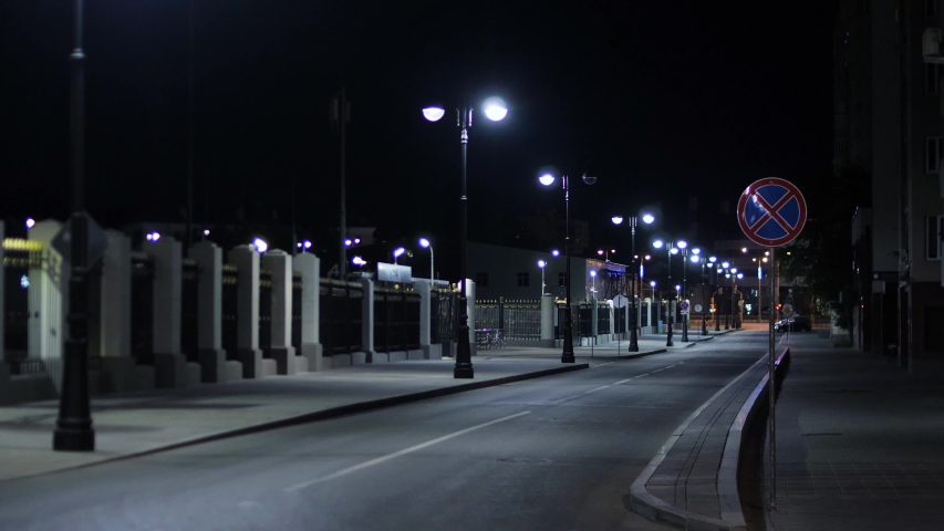 Empty roadway lit by lanterns on night. Stock footage. Summer night in city illuminated by white lights empties on roads at later time | Shutterstock HD Video #1035933458