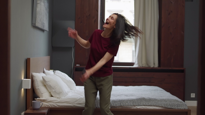 Tracking shot of happy mature woman dancing joyfully near bed in domestic bedroom or hotel room, celebrating good news with cell phone in her hand #1035935477