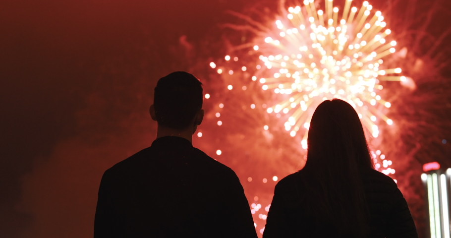 Happy couple in love looking at the sky and enjoys the party. Silhouette of people watching explosive and colorful fireworks in the evening sky. Holiday event and celebration. People have fun.